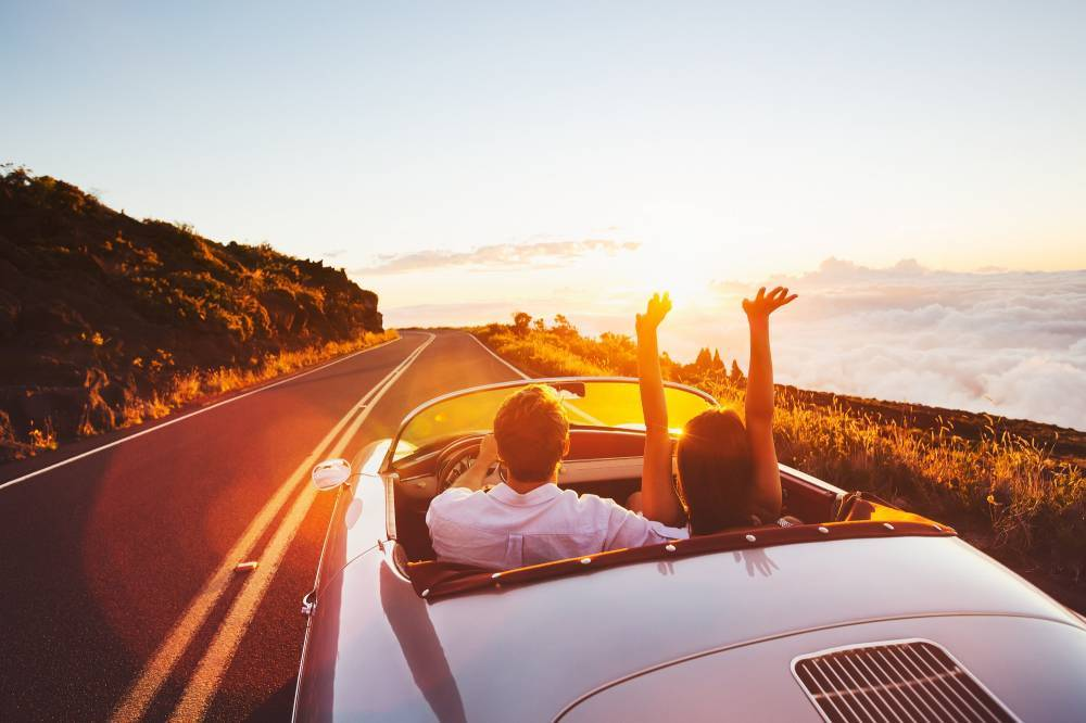 Un jeune couple dans une voiture décapotable sur une route de campagne avec un couché de soleil.